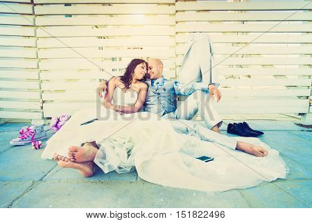 Young newlyweds having an emotional rest together after wedding ceremony - Life and love concept with lovely couple of groom and bride - Lower view point composition with soft lomo vignetted filter