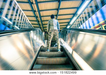Man standing on treadmills escalator stairway with soft motion blur - Urban life travel concept with street fashion guy at subway underground train station - Slight desaturated vintage filtered look
