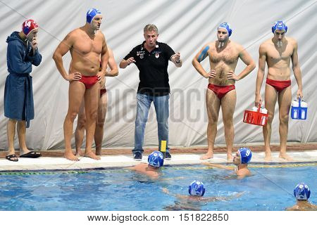 KAPOSVAR, HUNGARY - OCTOBER 5: Lajos Vad Honved trainer (in black) in action at a Hungarian championship water-polo game Kaposvar (white) vs. Honved (blue) on October 5, 2016 in Kaposvar, Hungary