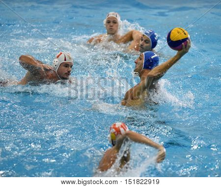 KAPOSVAR, HUNGARY - OCTOBER 5: Gergely Kiss (blue 7) in action at a Hungarian national championship water-polo game between Kaposvar (white) and Honved (blue) on October 5, 2016 in Kaposvar, Hungary