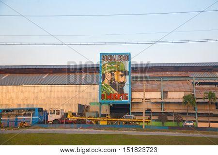 HAVANA, CUBA - FEB 6, 2011: Old factory in Havana with comunist propaganda featuring the image of Fidel Castro, cuban president until 2008.