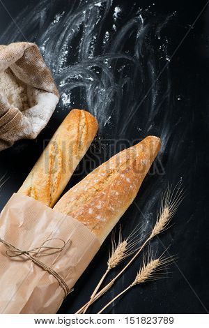 Top view of loaves of french baguette bread tied together with paper and string decorated with wheat ears on a floured black background.