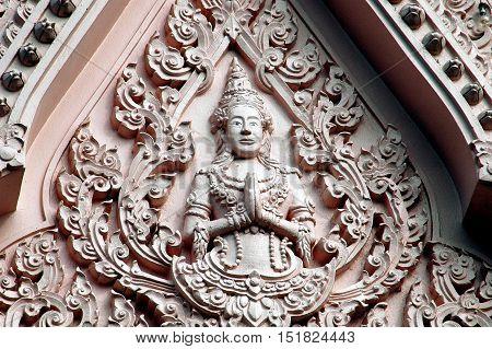 Nakhon Pathom Thailand - December 27 2005: Buddha with clasped hands decorates the North Vihara tympanum at Wat Phra Pathom Chedi