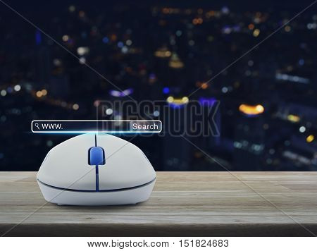 Wireless computer mouse with search www button on wooden table over blur light city tower Searching system and internet concept