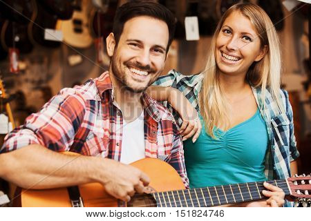 Young couple in musical instruments store looking for  guitar.
