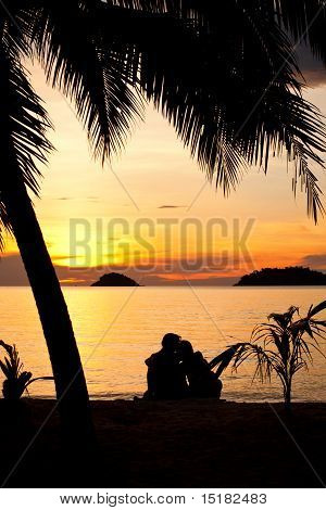 Silhouette Of A Romantic Couple Sitting On A Beach At Sunset