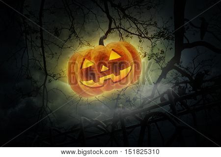 Jack O Lantern pumpkin over old fence dead tree moon and cloudy sky Mystery background Halloween concept