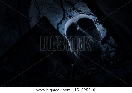 Human skull with old fence over old grunge castle dead tree moon and cloudy sky Spooky background Halloween concept