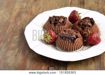 Delicious chocolate souffle with prunes and strawberries sprinkled with cocoa, copy space