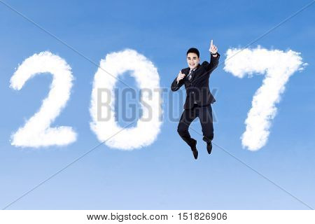 Young Asian businessman wearing formal suit and jumping on the blue sky with clouds shaped number 2017