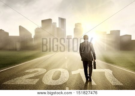 Back view of businessman carrying bag and walking on the street with numbers 2017 and bright sunlight