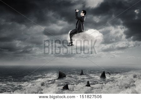 Young Asian businessman looking through binoculars while sitting on the cloud above dangerous sharks on the sea