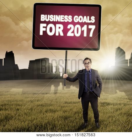 Young businessman standing at the field while holding a billboard with business goals for 2017