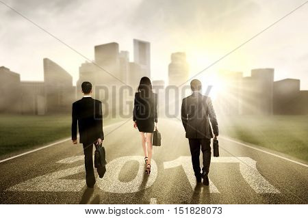 Group of businesspeople walking on the road with number 2017 and bright sunlight