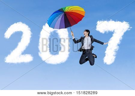 Joyful Asian businesswoman jumping on the blue sky while holding a colorful umbrella with cloud shaped number 2017