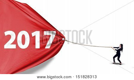 Young Asian businesswoman pulling number 2017 on a red banner with a rope isolated on white background