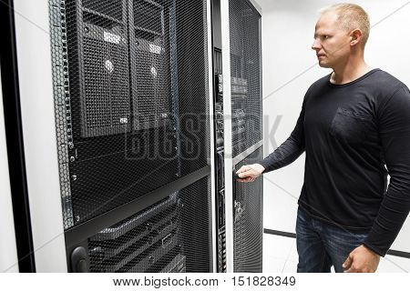 Mid adult male technician opening server rack door in large data center