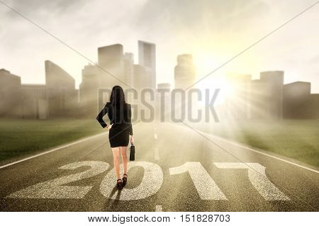 Image of a businesswoman walking on the street while carrying a briefcase with number 2017