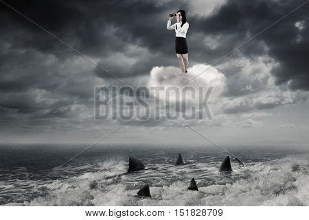 Young businesswoman standing on the cloud and looking through binoculars above sharks on the sea