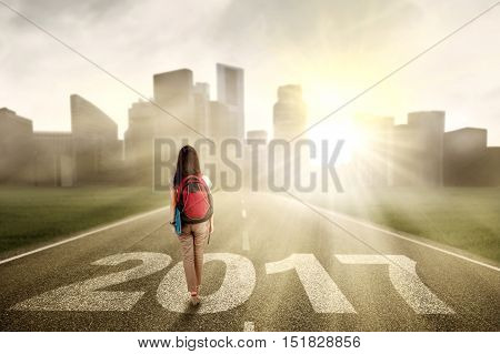 Female college student walking on the road while carrying bag with numbers 2017