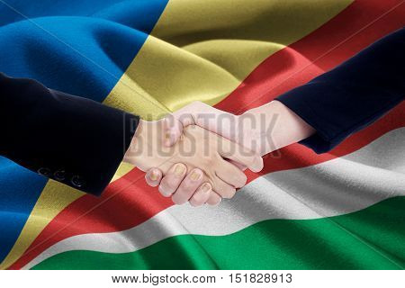 Image of cooperation handshake with two entrepreneur hands closing a meeting by shaking hands with flag of Seychelles