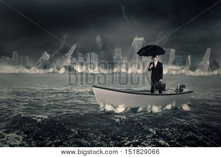 Young businessman standing on the boat while holding an umbrella and briefcase with a sinking town at the sea