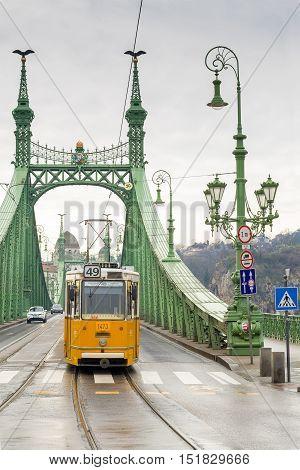 Yellow Tram On The Liberty Bridge In Budapest, Hungary.