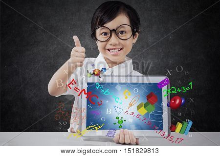 Little girl showing thumb up while holding a digital tablet with formula of science math and physics on the screen