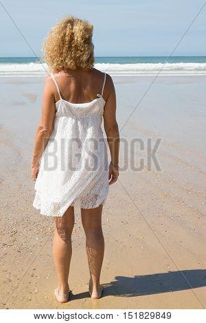 Beautiful Blond Girl On The Beach Alone