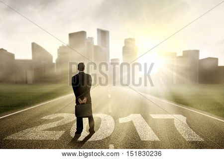 Image of a male entrepreneur standing on the highway with numbers 2017 and bright sunlight