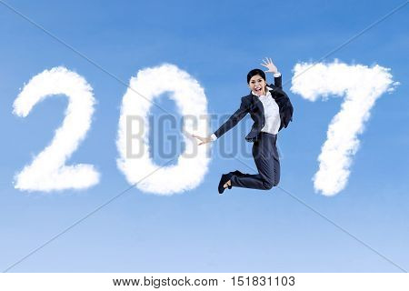 Successful Asian businesswoman wearing formal suit and jumping on the sky with cloud shaped number 2017