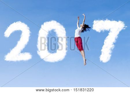 Concept of New Year 2017. Young woman dancing on the blue sky with clouds shaped number 2017