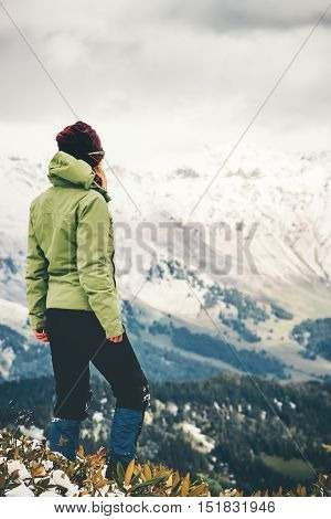 Woman Traveler standing alone Lifestyle adventure concept snow mountains on background winter vacations