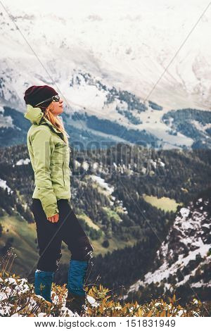 Woman Traveler standing alone on cliff enjoying landscape Travel Lifestyle adventure concept snow mountains on background active vacations