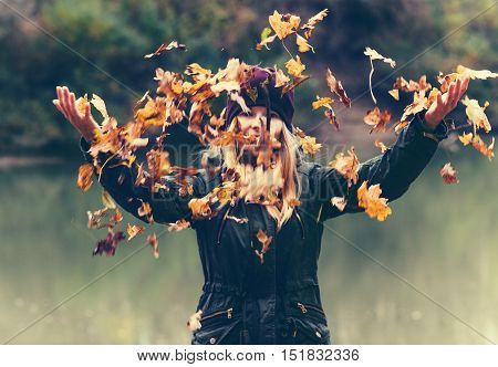 Young Woman playing with autumn leaves in park raised hands walking outdoor Lifestyle nature on background