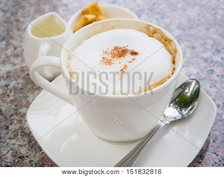 White cup of cappuccino stands on the rock table selective focus