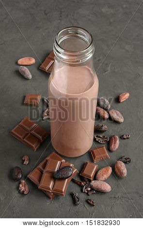 Chocolate Milk In A Glass Bottle With Pieces Of Chocolate Bar And Cacao Beans