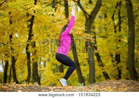 Sporty beautiful young woman practicing yoga, standing in Chair Pose, Fierce, Wild, Awkward posture, Utkatasana, working out outdoors in autumn park wearing bright sportswear. Full length, side view