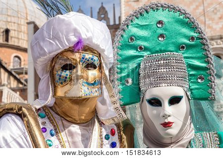 VENICE, ITALY - FEBRUARY 15, 2015: Two models disguised with traditional venetian costumes, posing in San Marco square during the Carnival of Venice
