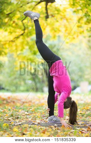 Sporty beautiful young woman practicing yoga, doing standing split pose, urdhva prasarita eka padasana, working out outdoor on autumn day wearing bright sportswear sweatshirt. Full length, side view