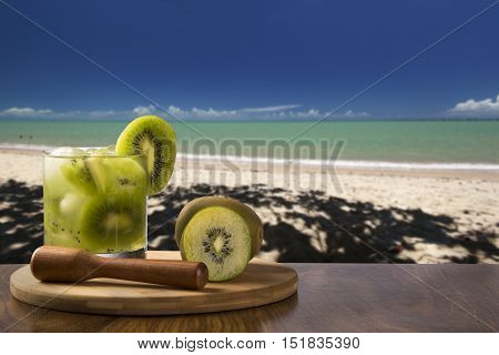 Kiwi Fruit Caipirinha Of Brazil Over Beautiful Beach Background