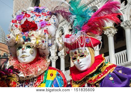VENICE, ITALY - FEBRUARY 15, 2015:Two models disguised with colorful carnival costumes, posing in San Marco square during the Carnival of Venice
