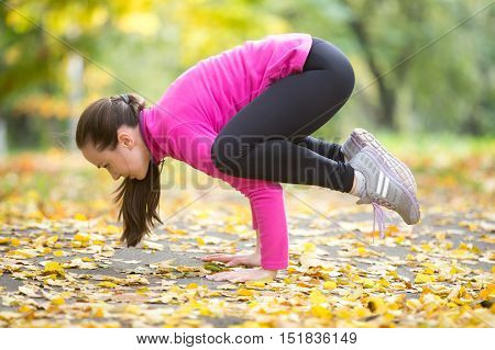 Sporty beautiful young woman practicing yoga, doing armstand Crane, Crow Pose, Bakasana, working out outdoors in autumn park wearing bright sportswear. Full length, side view