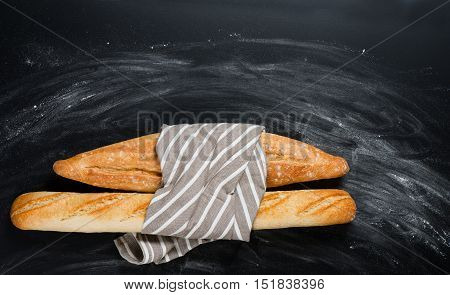 Top view of fresh baked traditional baguettes bread tied together with napkin on a floured black chalkboard with copy space.