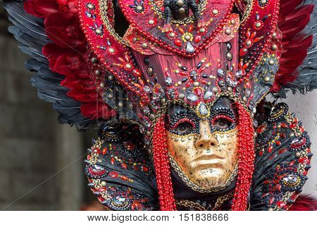 VENICE, ITALY - FEBRUARY 15, 2015: An unidentified person wearing a golden mask and a magnificent red costume at the Carnival of Venice