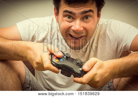 Emotional young addicted man playing video games in living room