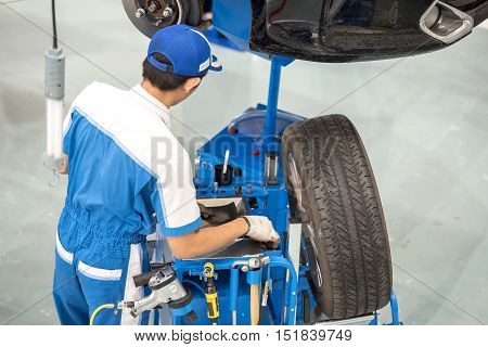 Auto mechanic changing car wheel in car care service center