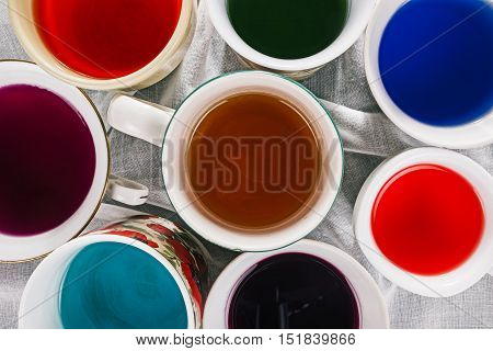 Colorful liquids in various cups and mugs. Flat lay