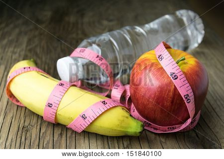 Healthy eating concept tape measure fruit and water bottle on a wooden background
