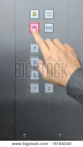 businessman hand press open door button in elevator